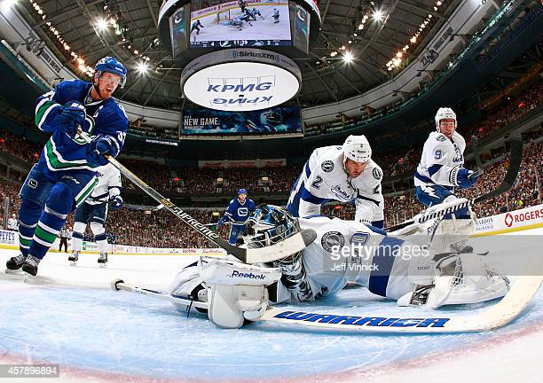 Ben Bishop of the Tampa Bay Lightning makes a save as Henrik Sedin of the Vancouver Canucks looks for a rebound during their NHL game at Rogers Arena...