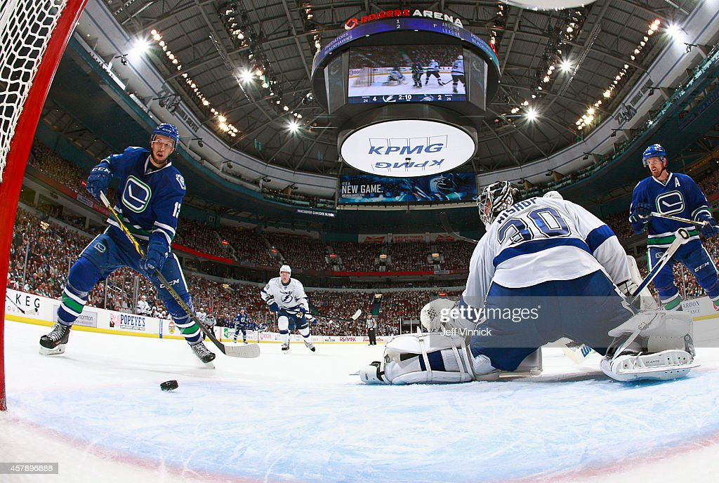 Ben Bishop #30 of the Tampa Bay Lightning makes a save as Nick Bonino #13 of the Vancouver Canucks looks for a rebound during their NHL game at Rogers Arena October 18, 2014 in Vancouver, British Columbia, Canada.