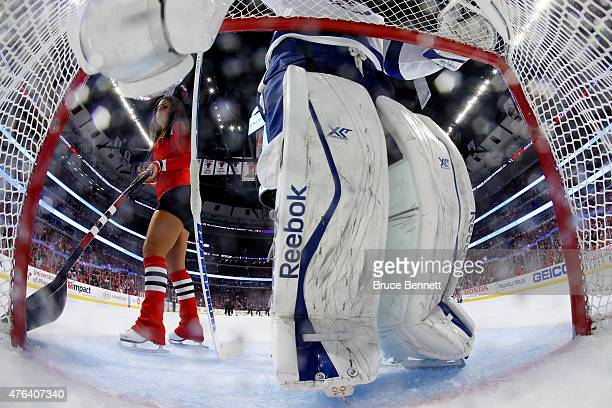 Ben Bishop of the Tampa Bay Lightning stays in position as a member of the ice crew tries to clear the crease during Game Three of the 2015 NHL...
