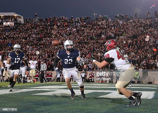 Ben Braunecker of the Harvard Crimson catches a touchdown pass by the defense Matthew Oplinger of the Yale Bulldogs in the second half on November 21...