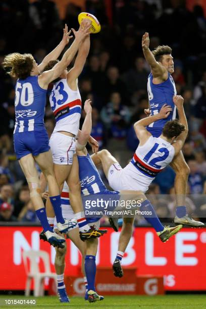 Ben Brown of the Kangaroos and Aaron Naughton of the Bulldogs fly for the ball as Jarrad Waite of the Kangaroos collides with Zanie Cordy during the...