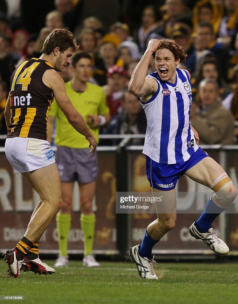 Ben Brown of the Kangaroos celebrates a goal next to Grant Birchall of the Hawks during the round 16 AFL match between North Melbourne Kangaroos and the Hawthorn Hawks at Etihad Stadium on July 4, 2014 in Melbourne, Australia.