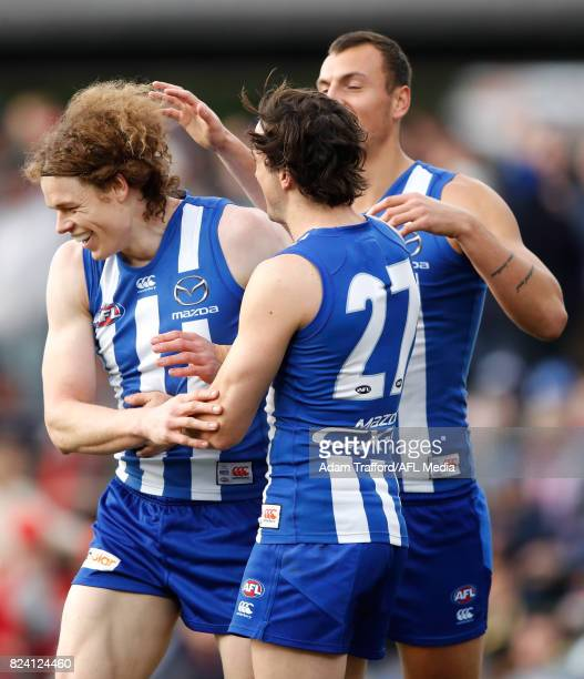 Ben Brown of the Kangaroos celebrates a goal with teammates Taylor Garner and Braydon Preuss during the 2017 AFL round 19 match between the North...