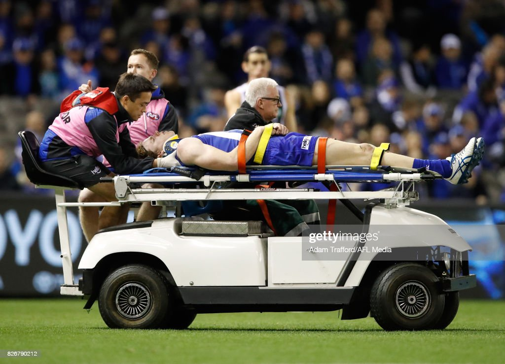 Ben Brown of the Kangaroos comes off the ground injured after being tackled by Brodie Grundy of the Magpies during the 2017 AFL round 20 match between the North Melbourne Kangaroos and the Collingwood Magpies at Etihad Stadium on August 05, 2017 in Melbourne, Australia.