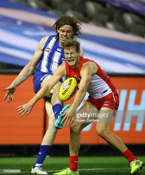 Ben Brown of the Kangaroos has his kick smothered by Jordan Dawson of the Sydney Swans during the round 3 AFL match between the North Melbourne...