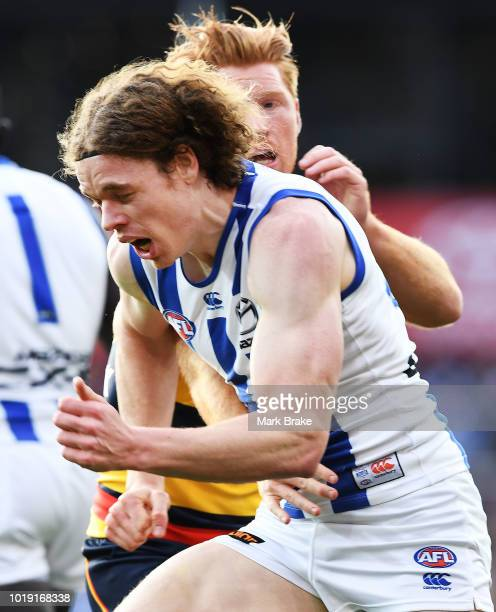 Ben Brown of the Kangaroos is held off ball by Kyle Cheney of the Adelaide Crows during the round 22 AFL match between the Adelaide Crows and North...