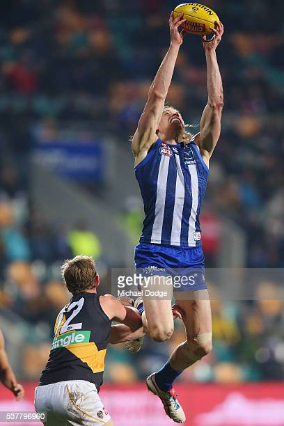 Ben Brown of the Kangaroos marks the ball David Astbury of the Tigers during the round 11 AFL match between the North Melbourne Kangaroos and the...