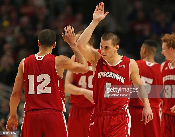 Ben Brust of the Wisconsin Badgers celebrates with teammate Traevon Jackson during a semifinal game of the Big Ten Basketball Tournament against the...