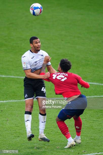 Ben Cabango of Swansea City under pressure from Josh Koroma of Huddersfield Town during the Sky Bet Championship match between Swansea City and...