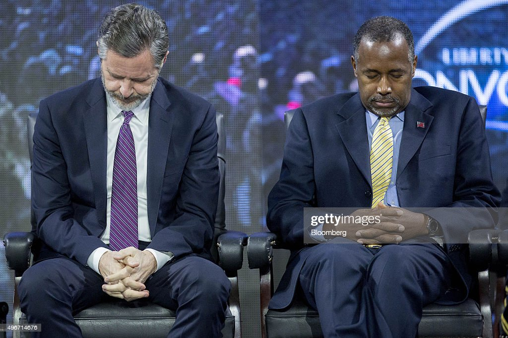 Ben Carson, 2016 Republican presidential candidate, right, and Jerry Falwell Jr., president of Liberty University, listen to a prayer during a Liberty University Convocation in Lynchburg, Virginia, U.S., on Wednesday, Nov. 11, 2015. As retired neurosurgeon Carson has risen in the polls, media reports have revisited his accounts of acts of violence as a child, a key part of the redemption story he discusses on the campaign trail. Photographer: Andrew Harrer/Bloomberg via Getty Images