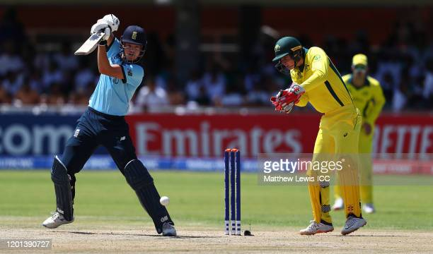 Ben Charlesworth of England hits the ball towards the boundary as Patrick Rowe of Australia looks on during the ICC U19 Cricket World Cup Group B...