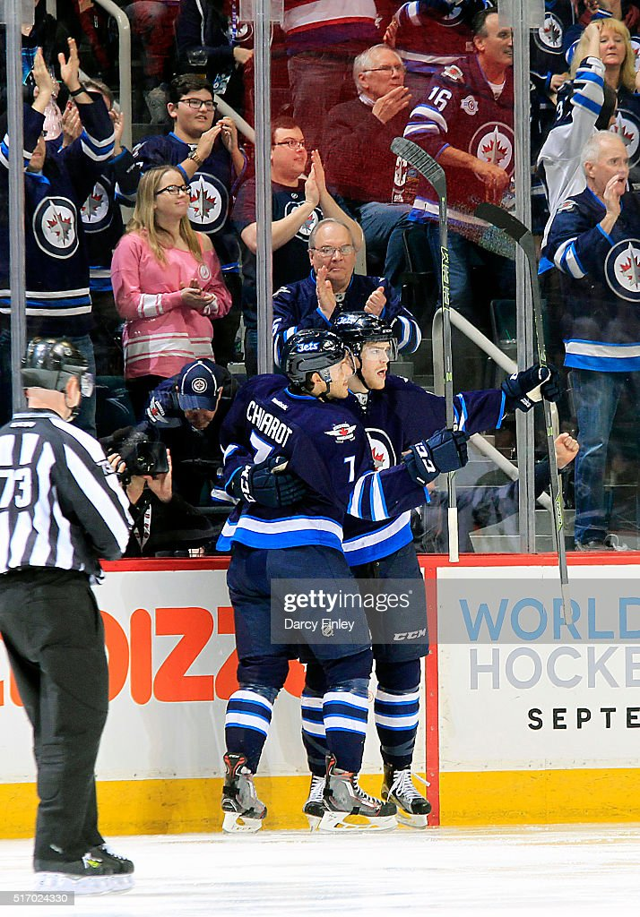 Ben Chiarot #7 and Adam Lowry #17 of the Winnipeg Jets celebrate a third period goal against the Vancouver Canucks at the MTS Centre on March 22, 2016 in Winnipeg, Manitoba, Canada.