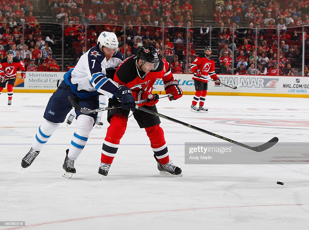 Ben Chiarot #7 of the Winnipeg Jets and Lee Stempniak #20 of the New Jersey Devils battle for a loose puck during the game at the Prudential Center on October 9, 2015 in Newark, New Jersey.