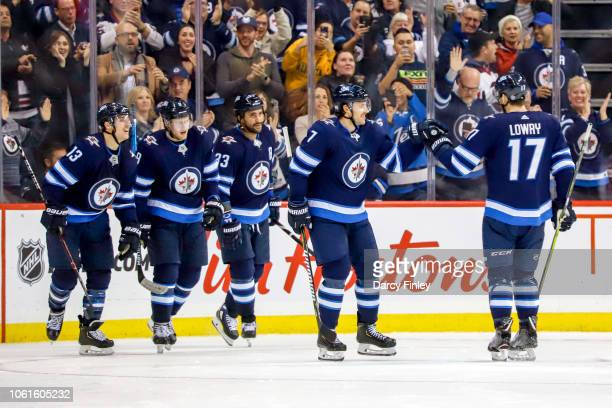 Ben Chiarot of the Winnipeg Jets celebrates his third period goal against the Washington Capitals with teammate Adam Lowry as they leave the ice at...