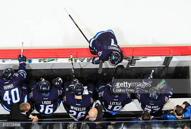 Ben Chiarot of the Winnipeg Jets chats with teammates Blake Wheeler and Bryan Little at the bench during a third period stoppage in play against the...