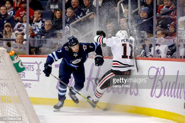 Ben Chiarot of the Winnipeg Jets checks Brendan Perlini of the Chicago Blackhawks into the boards during third period action at the Bell MTS Place on...