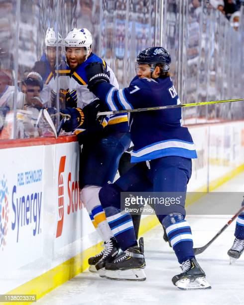 Ben Chiarot of the Winnipeg Jets checks Pat Maroon of the St Louis Blues into the boards during third period action in Game Five of the Western...