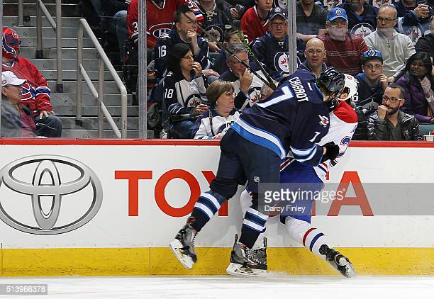 Ben Chiarot of the Winnipeg Jets checks Phillip Danault of the Montreal Canadiens along the boards during third period action at the MTS Centre on...