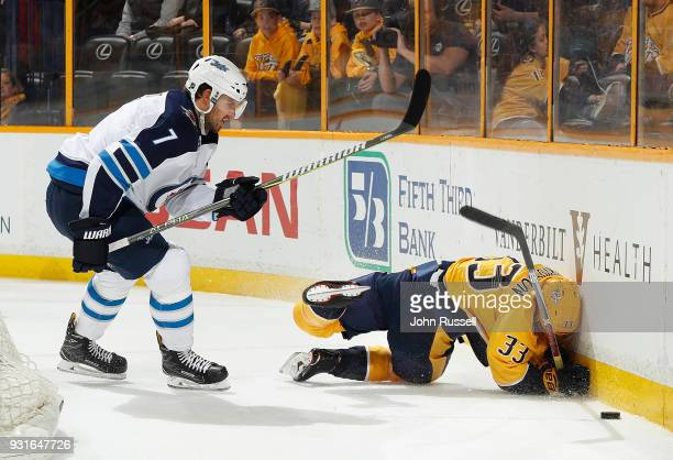 Ben Chiarot of the Winnipeg Jets checks Viktor Arvidsson of the Nashville Predators into the boards during an NHL game at Bridgestone Arena on March...