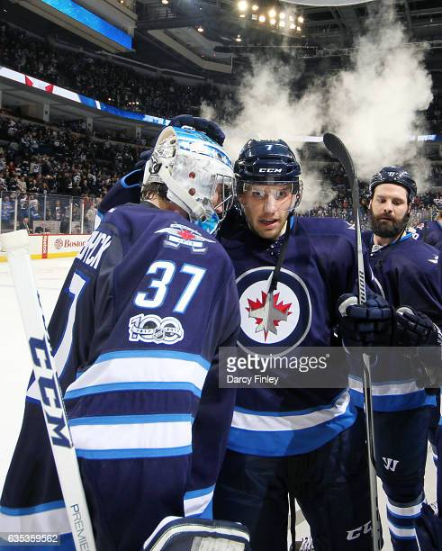 Ben Chiarot of the Winnipeg Jets congratulates goaltender Connor Hellebuyck after a 52 victory over the Dallas Stars at the MTS Centre on February 14...