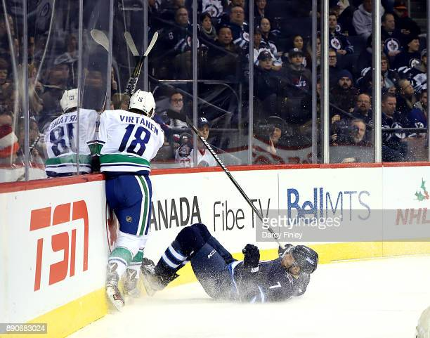 Ben Chiarot of the Winnipeg Jets falls to the ice after colliding along the boards with Jake Virtanen of the Vancouver Canucks during third period...