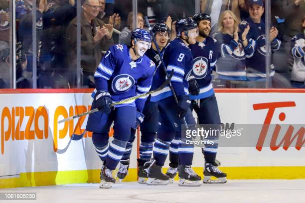 Ben Chiarot of the Winnipeg Jets is all smiles as he leads teammates Brandon Tanev Andrew Copp and Dustin Byfuglien off the ice following his third...
