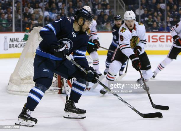 Ben Chiarot of the Winnipeg Jets looks to pass as Connor Murphy of the Chicago Blackhawks defends during NHL action on April 7 2018 at Bell MTS Place...