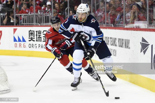 Ben Chiarot of the Winnipeg Jets skates with the puck against Travis Boyd of the Washington Capitals in the third period at Capital One Arena on...
