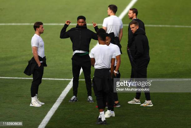 Ben Chilwell Joe Gomez and Jordan Henderson walk on the pitch with team mates during England media access on the eve of their UEFA Nations League...