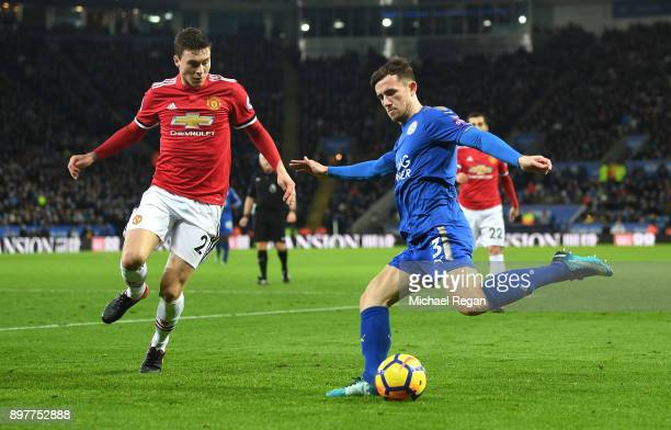 Ben Chilwell of Leicester City crosses with Victor Lindelof of Manchester United during the Premier League match between Leicester City and...