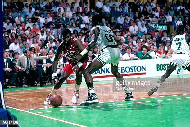 Ben Coleman of the Philadelphia 76ers makes a move to the basket against Robert Parish of the Boston Celtics during a game played in 1989 at the...