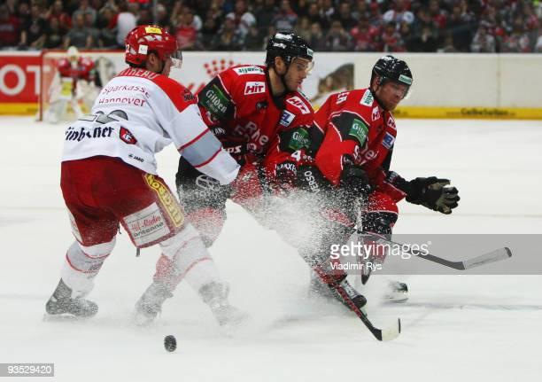 Ben Cottreau of Scorpions defends as Daniel Rudslaett and Moritz Mueller of Haie attack during the Deutsche Eishockey Liga game between Koelner Haie...