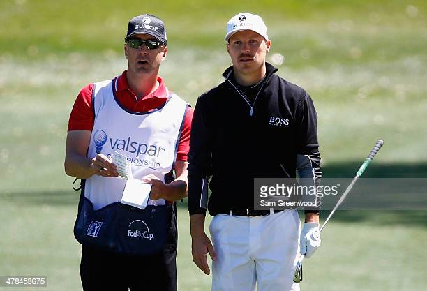Ben Crane assesses a shot with his caddie on the 18th hole during the first round of the Valspar Championship at Innisbrook Resort and Golf Club on...