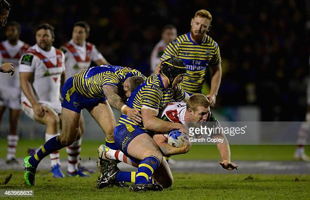 Ben Creagh of St George Illawarra Dragons is tackled by Chris Hill of Warrington Wolves during the World Club Series match between Warrington Wolves...