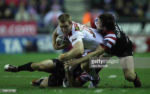 Ben Creagh of St George Illawarra Dragons is tackled by Martin Gleeson of Wigan Warriors during the World Club Challenge match between Wigan Warriors...