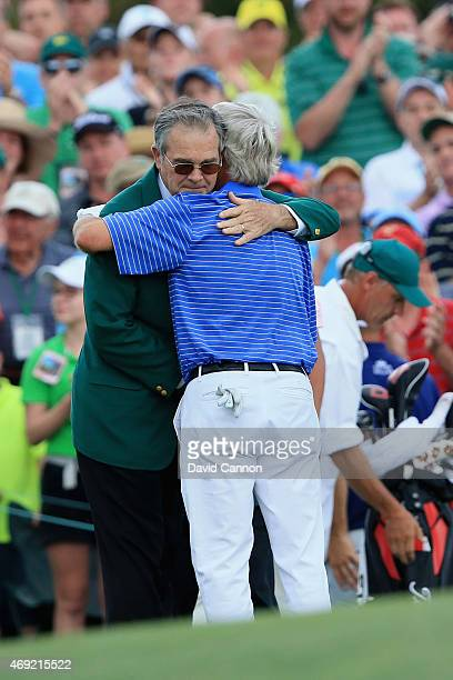 Ben Crenshaw of the United States hugs William Porter Payne Chairman of Augusta National behind the 18th green after playing his final Masters during...