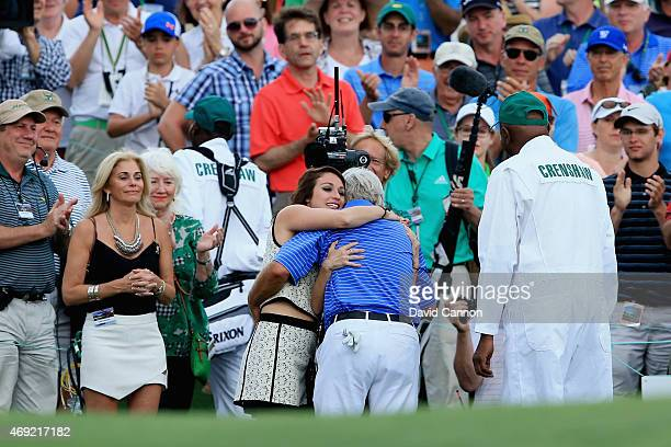 Ben Crenshaw of the United States is greeted by his wife Julie and their daughters behind the 18th green after playing his final Masters during the...