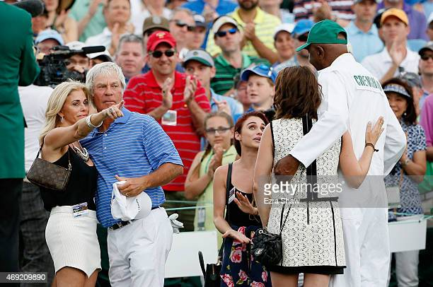Ben Crenshaw of the United States waits alongside his wife Julie their daughters and longtime caddie Carl Jackson behind the 18th green after playing...