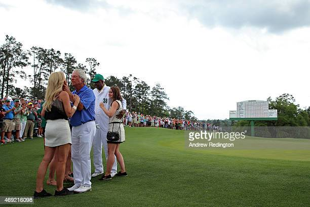Ben Crenshaw of the United States waits alongside his wife Julie their family and longtime caddie Carl Jackson behind the 18th green after playing...