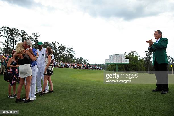 Ben Crenshaw of the United States waits with his wife Julie their family and longtime caddie Carl Jackson as William Porter Payne Chairman of Augusta...