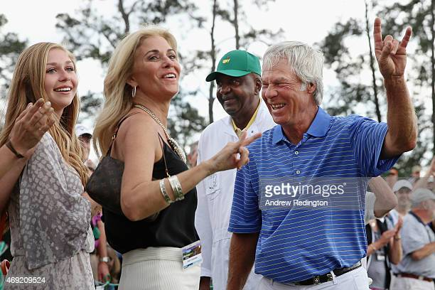 Ben Crenshaw of the United States waves to the gallery alongside his wife Julie and caddie Carl Jackson behind the 18th green after playing his final...