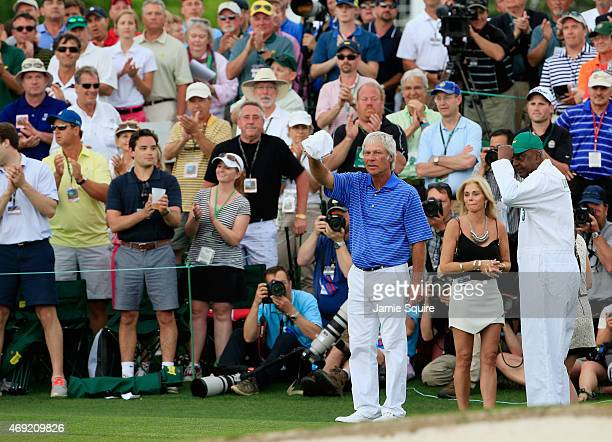 Ben Crenshaw of the United States waves to the gallery alongside his wife Julie and longtime caddie Carl Jackson behind the 18th green after playing...