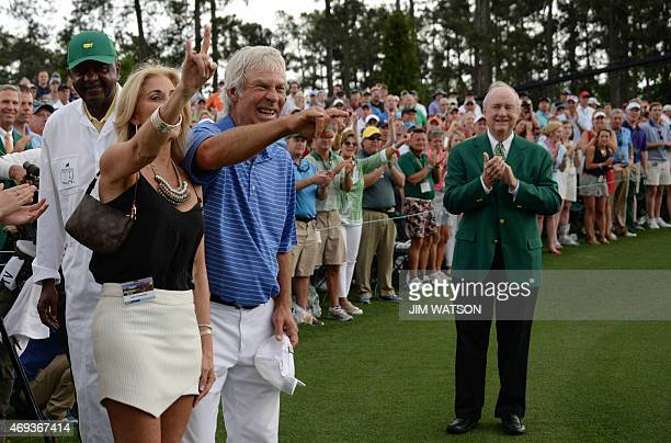 Ben Crenshaw of the US gestures to the crowd with his wife Julie after finishing the 18th hole during Round 2 of the 79th Masters Golf Tournament at...