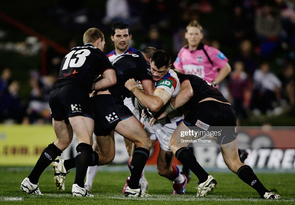 Ben Cross of the Knights is tackled by the Panthers defence during the round 13 NRL match between the Penrith Panthers and the Newcastle Knights at CUA Stadium on June 5, 2010 in Sydney, Australia.