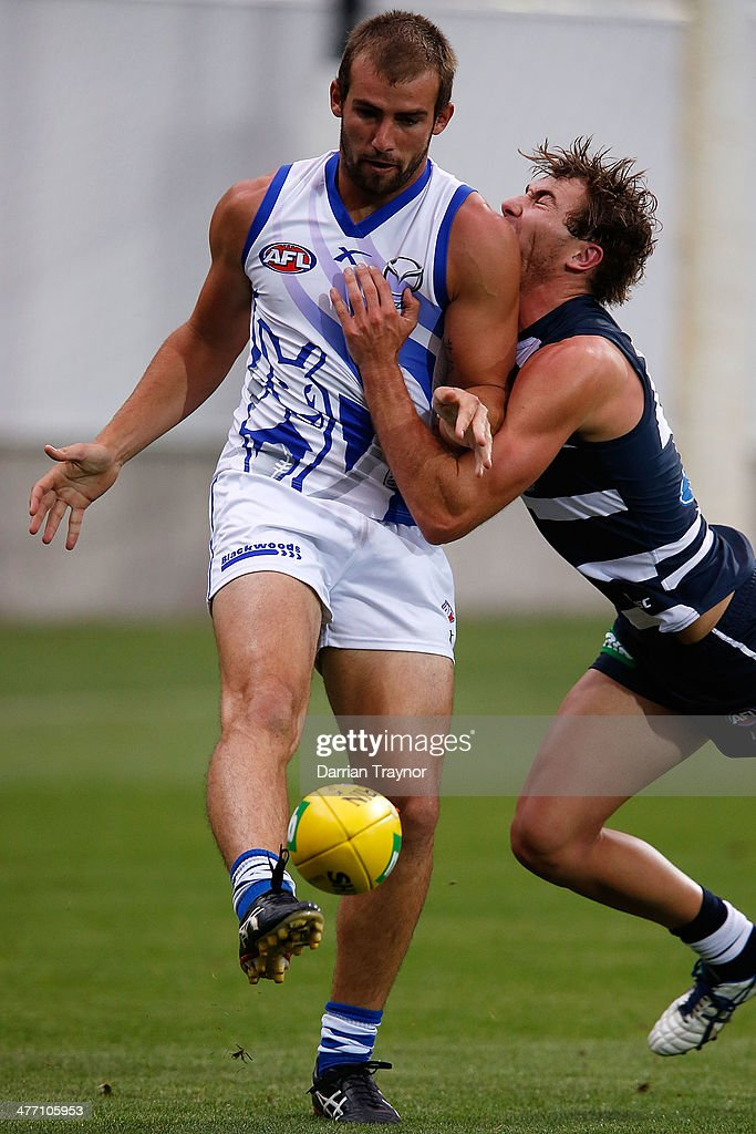 Ben Cunnington of North Melbourne kicks the ball as Jackson Thurlow of Geelong attempts to tackle during the AFL Practice Match between the Geelong Cats and the North Melbourne Kangaroos at Simonds Stadium on March 7, 2014 in Geelong, Australia.