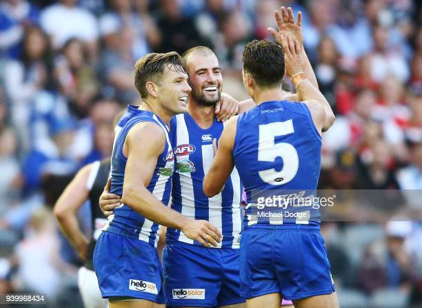 Ben Cunnington of the Kangaroos celebrates a goal with Shaun Higgins and Ben Jacobs during the round two AFL match between the North Melbourne...