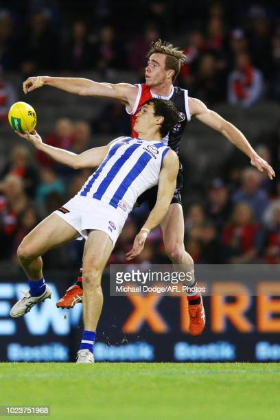 Ben Cunnington of the Kangaroos competes for the ball under Ben Paton of the Saints during the round 23 AFL match between the St Kilda Saints and the...