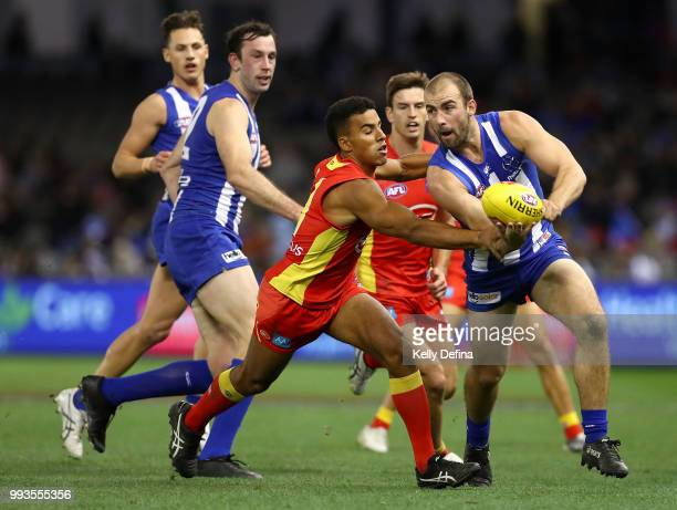 Ben Cunnington of the Kangaroos handballs during the round 16 AFL match between the North Melbourne Kangaroos and the Gold Coast Suns at Etihad...