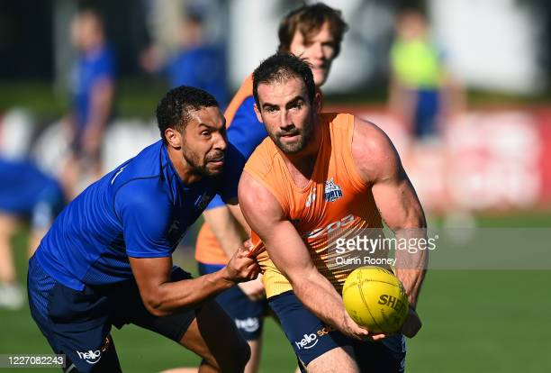 Ben Cunnington of the Kangaroos handballs whilst being tackled by Aiden Bonar during a North Melbourne Kangaroos AFL training session at Arden Street...
