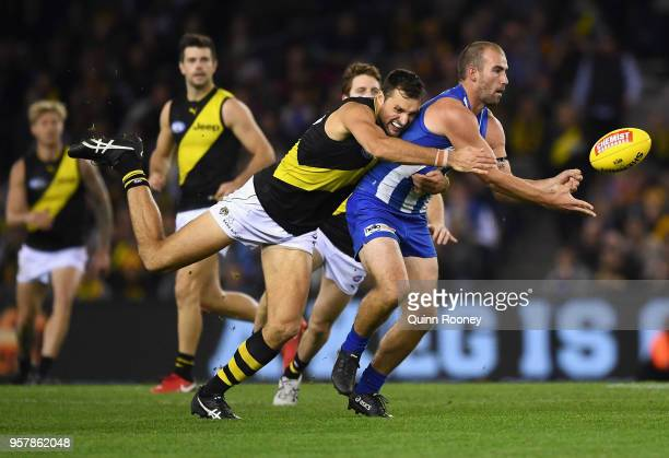 Ben Cunnington of the Kangaroos handballs whilst being tackled by Toby Nankervis of the Tigers during the round eight AFL match between the North...